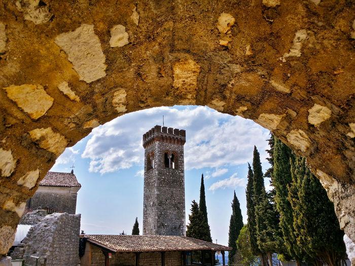 Castello di caneva against sky seen through arch