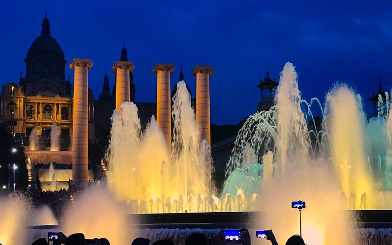 Panoramic view of fountain against buildings at night