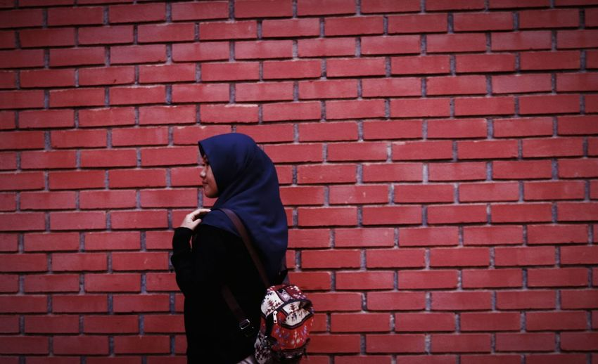 Side view of woman wearing hijab walking by brick wall