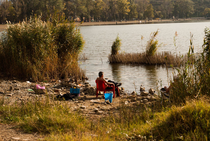 Beauty In Nature Fishing Lake Leisure Activity Nature Outdoors Real People Relaxation Sitting Water Weekend Activities