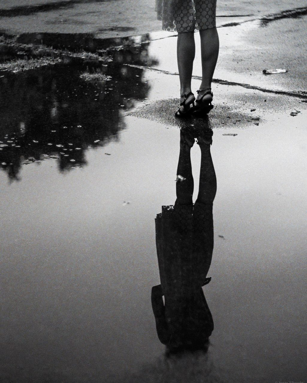 LOW SECTION VIEW OF WOMAN STANDING ON WET STREET