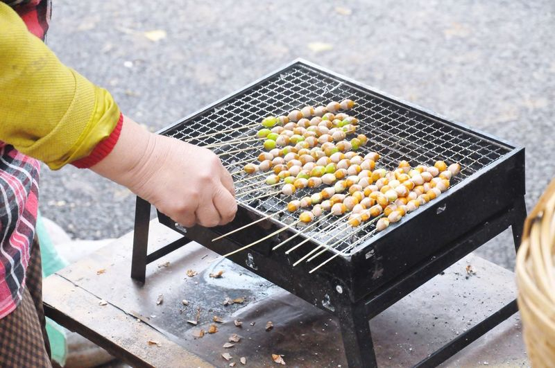 Midsection Of Woman Preparing Marshmallow On Barbecue Grill