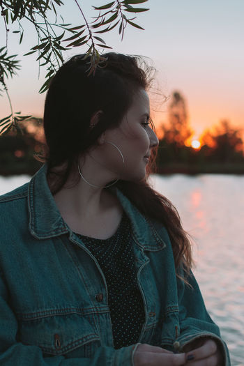 Beautiful woman standing by lake against sky during sunset