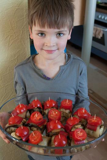 Portrait of boy holding beef kebabs in glass casserole