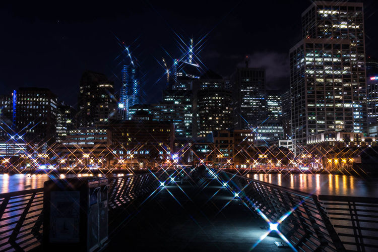 Illuminated boardwalk and cityscape at night