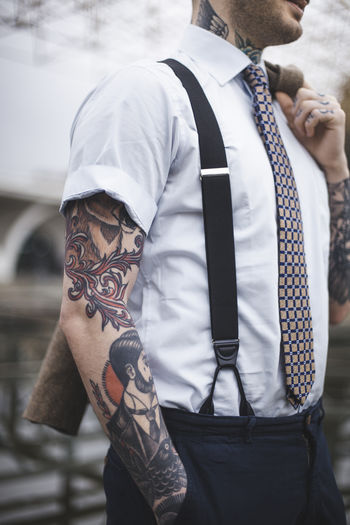 Midsection of tattooed man standing outdoors