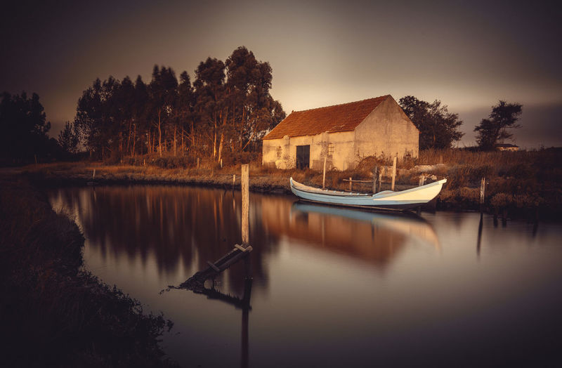 Boats in lake by buildings against sky