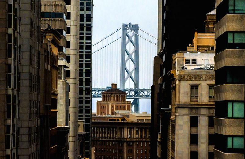 Buildings against bay bridge in city