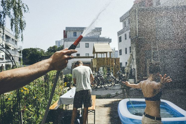 Cropped Hand Holding Pipe With Water Splashing On Woman By Buildings Against Sky