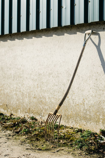 A rake standing against a wall. Agriculture Hayfork Outdoors Pitchfork Rake Sunny Wall