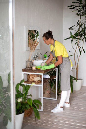 Side view of woman standing by potted plant at home