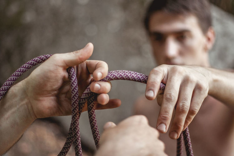 Close-Up Of Hands Holding Rope