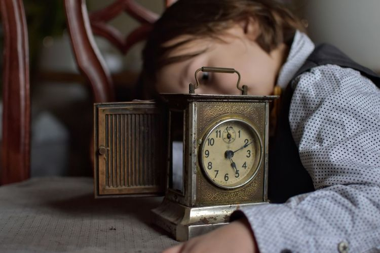 Close-up of boy with vintage clock on table