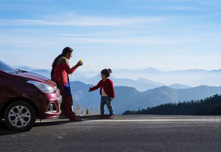Mother and daughter on a road trip. car travel vacation concept photo against himalayan mountain.