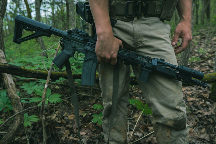 Low section of man holding a rifle in forest