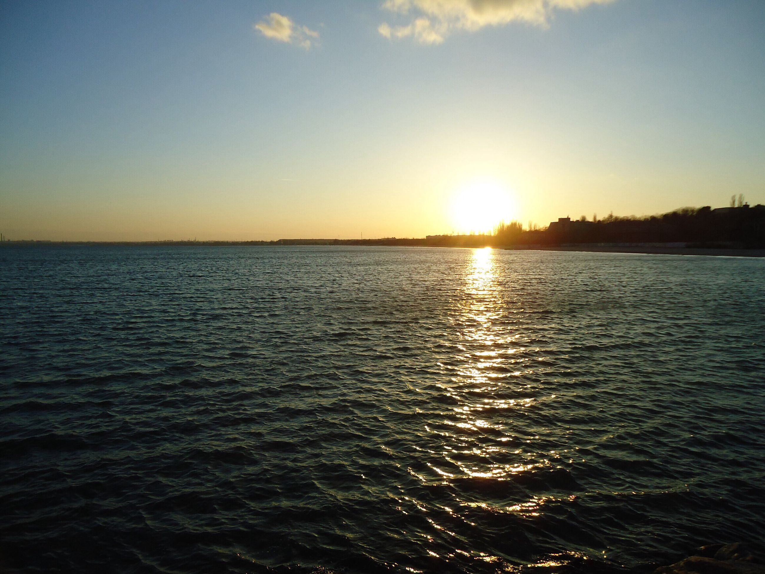water, sunset, sea, sun, scenics, tranquil scene, waterfront, beauty in nature, tranquility, rippled, reflection, nature, idyllic, sky, horizon over water, sunlight, orange color, seascape, outdoors, sunbeam, no people, remote, calm, non-urban scene, ocean, majestic, blue, water surface