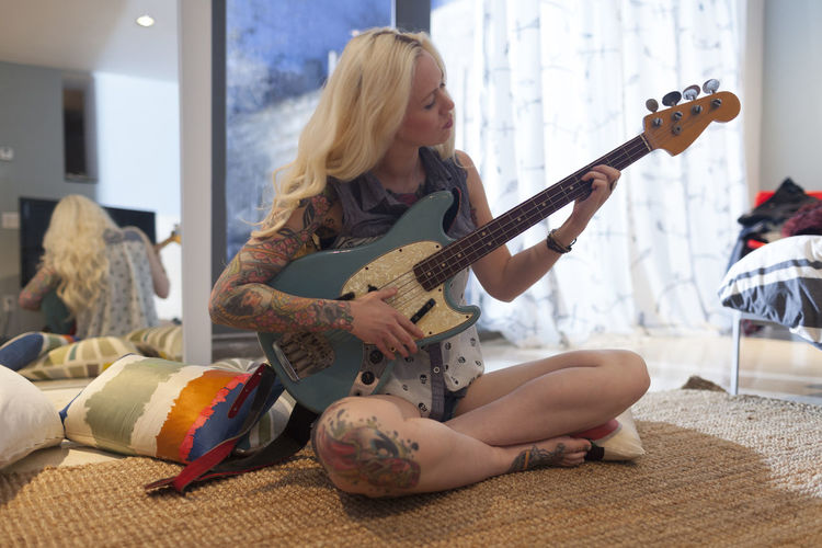 Woman playing guitar at home
