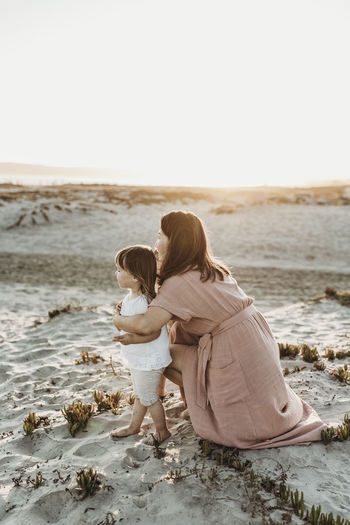 Rear view of mother and daughter on beach