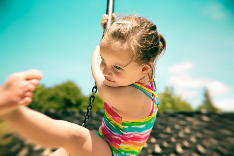 Girl Swinging On Chain Against Sky