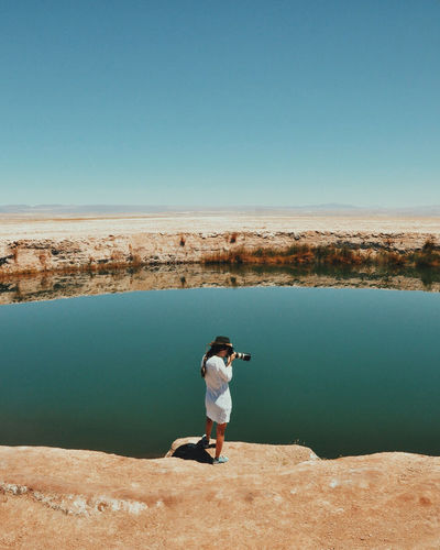 Woman Standing On Edge Of Cliff While Photographing Pond Against Clear Sky