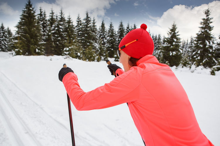 A woman cross-country skiing in the Alps Action, Activity, Adult, Competition, Cross-country, Female, Fit, Fitness, Forest, Healthy, Holidays, Langlauf, Lifestyles, Nordic, People, Running, Skating, Skiing, Snow, Sports, Style, Training, Winter, Woman Adult Beauty In Nature Clothing Cold Temperature Day Land Leisure Activity Lifestyles Nature One Person Outdoors Real People Rear View Red Snow Sport Tree Warm Clothing Winter