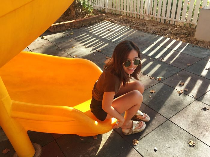 High angle view of smiling young woman wearing sunglasses sitting on slide in park