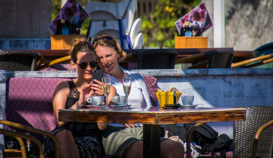 Friends using smart phone while sitting at outdoor cafe