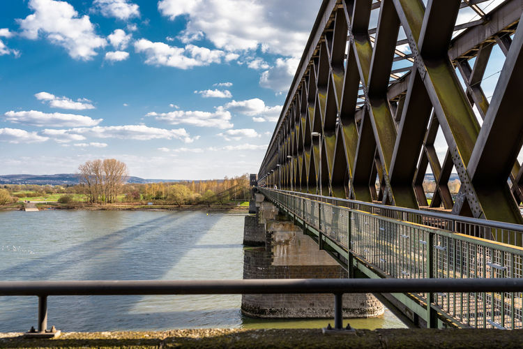 Steel, lattice structure of a railway bridge over a river with a background of blue sky with clouds