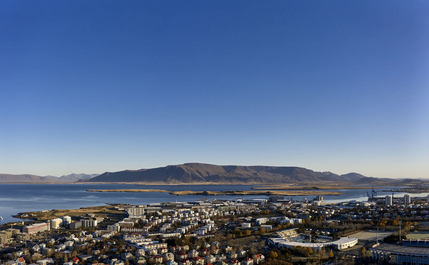 Panoramic view of city by sea against clear blue sky