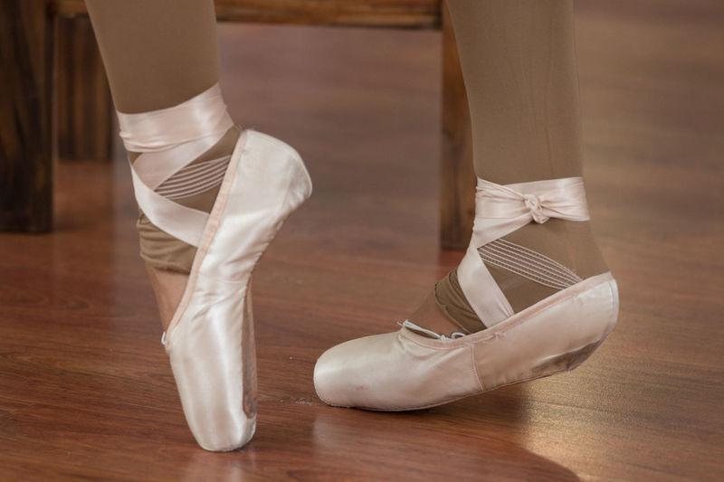 Low Section Of Ballerina Dancing On Hardwood Floor