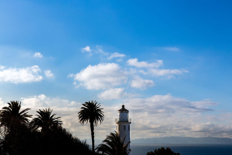 Lighthouse Architecture Beauty In Nature Blue Building Building Exterior Built Structure Cloud - Sky Day Low Angle View Nature No People Outdoors Palm Tree Plant Scenics - Nature Sea Sky Tower Tree Tropical Climate