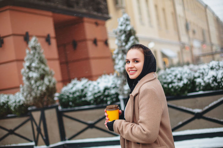 Portrait of woman holding coffee cup standing outdoors