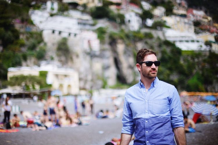 Tilt-shift image of handsome man standing at beach on sunny day