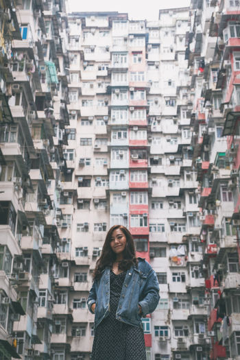 Portrait of woman standing against buildings in city