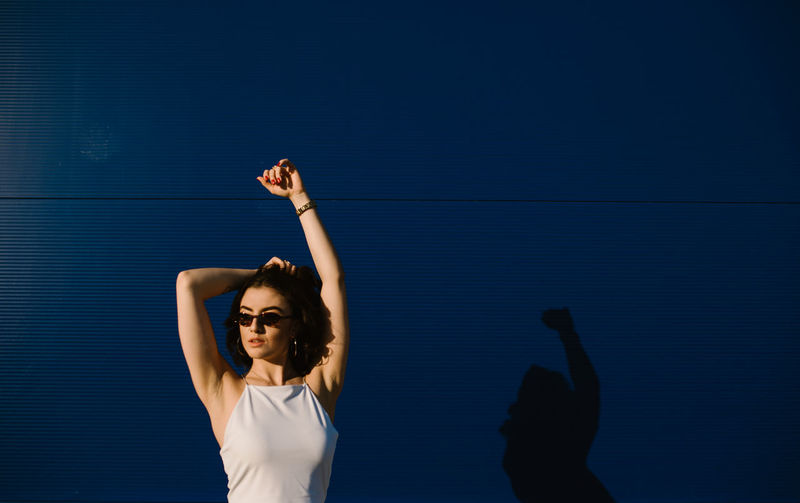 Woman standing against blue sky