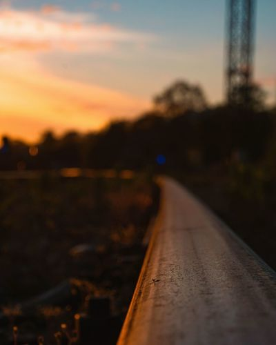 Close-up of railroad track against sky during sunset