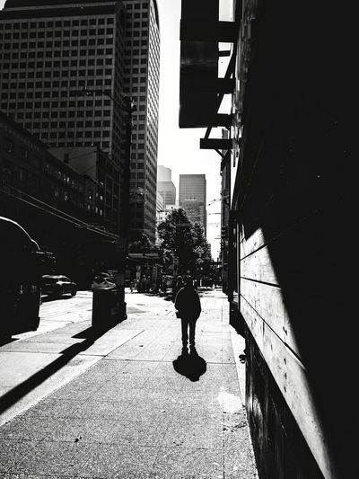 Rear view of man in city against sky