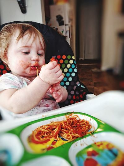 Cute baby girl eating spaghetti at home