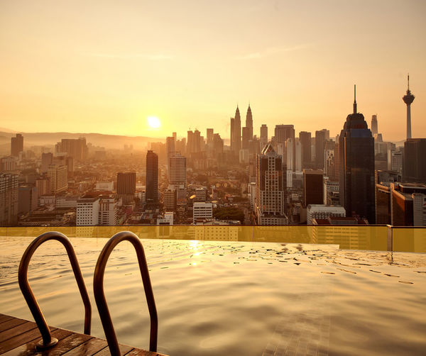 Infinity pool against buildings in city during sunset