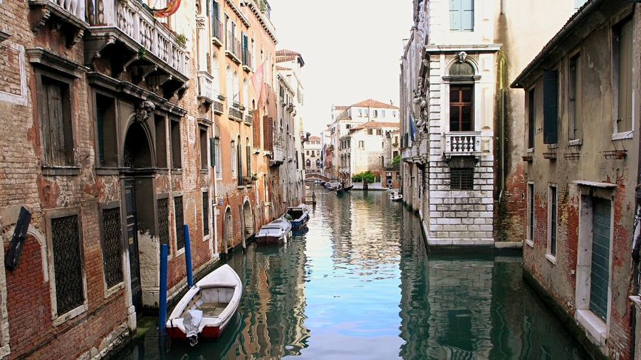 Boats moored at grand canal amidst buildings