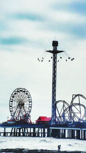 Amusement Park Rides By Sea Against Sky