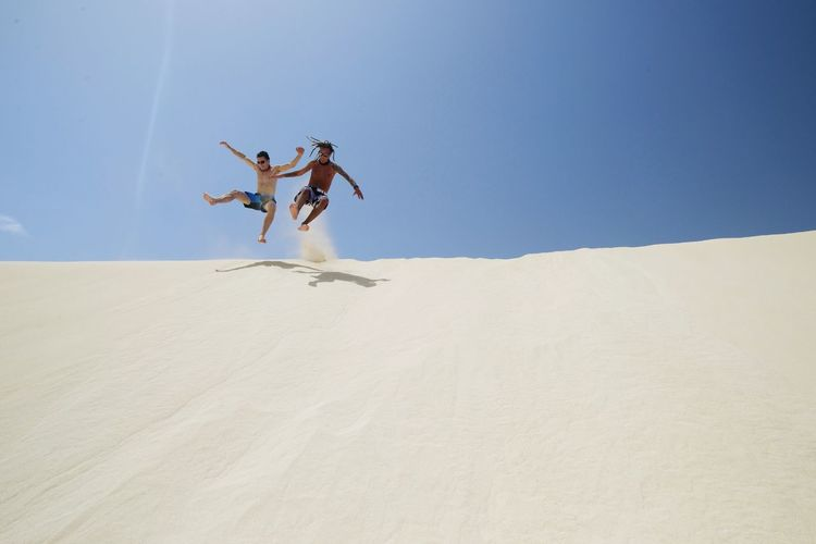 Low angle view of shirtless friends jumping on sand dune against blue sky