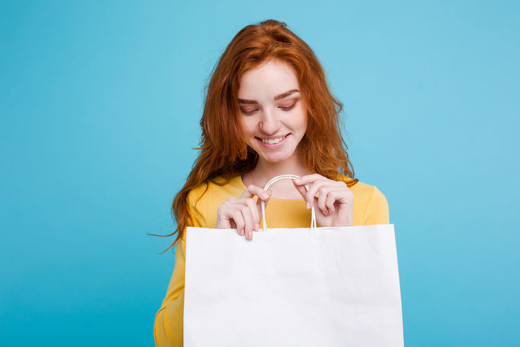 Smiling woman holding bag against blue background