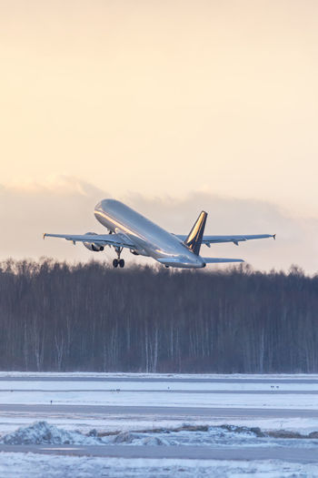 Airplane taking off during a sunset in winter time. aviation concept