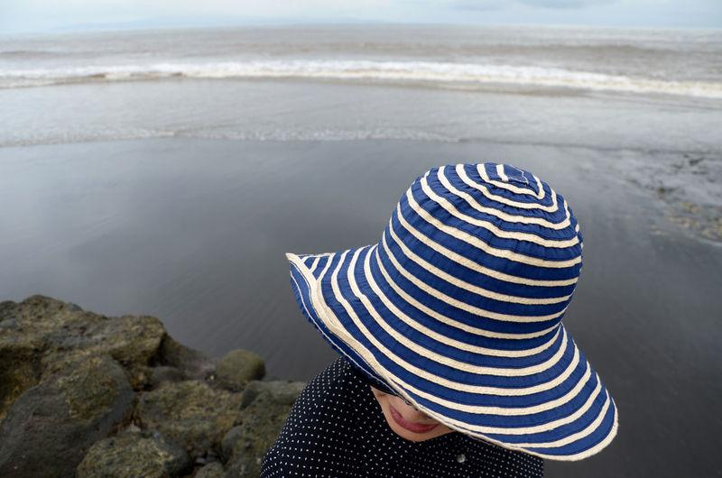 Woman in hat against sea