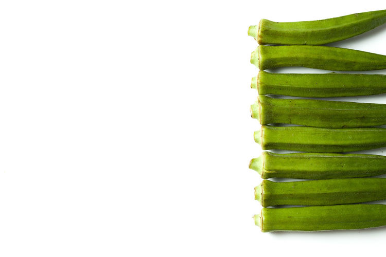 A fresh green okra isolated over white bakground Bending Cooking Cuisine Culinary Curry Diet Exotic Freshness Fruit Green Color Healthy Eating Heap Isolated Market Natural Nature Nutrition Okra Okra Plant Plant Raw Food Seed Vegetables