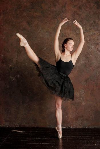 Ballet dancer posing against wall