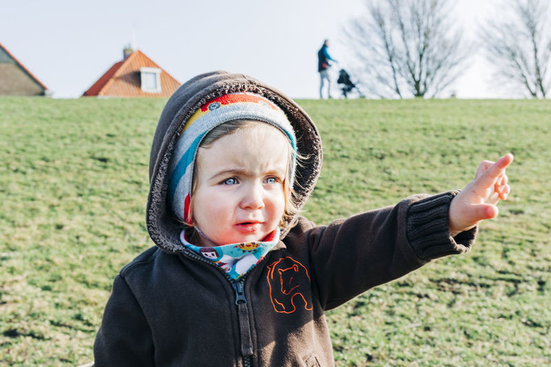 Toddler girl on grass pointing at something and man in background – Hindeloopen, Netherlands, Europe Head And Shoulders Arms Raised Human Hand Pointing Index Finger Human Finger Girl Girls Females The Way Forward Close-up Cardigan Cardigan Sweater Caucasian Germany Netherlands Dyke  Blue Eyes Exploring Showing Serious Roof Rooftop Adult Vacations Curiosity Man Distant Baby Stroller Standing Walking Wanderlust Hiking Hikingadventures Watching Grass Hand Arms Outstretched Confidence  Independence Child Childhood Field Portrait One Person Front View Real People Land Clothing Day Innocence Cute Lifestyles Nature Focus On Foreground Headshot Boys Males  Warm Clothing Outdoors