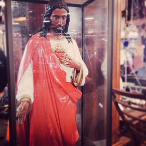 Statue of jesus christ in shop seen through glass