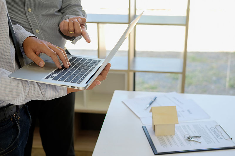 Midsection Of Real Estate Agent With Client Using Laptop At Office